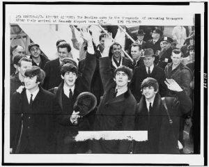 Billede af de fire medlemmer af the Beatles, John Lennon, Paul McCartney, George Harrison og Ringo Starr, hvis musik bliver spillet og historier fortalt ved vores festunderholdning, som ankommer til Kennedy Airport,